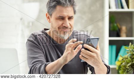 Bearded man working online with phone at home sitting at desk. Home office, browsing internet, reading news and social media. Portrait of mature age, middle age, mid adult man in 50s.