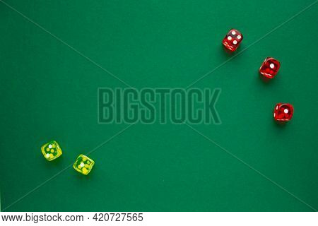 Three Red Dices And Two Yellow Dices On Green Background. Copy Space