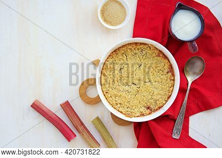 Dessert, Crispy Crumble With Rhubarb In A White Glass Form On A Light Concrete Background. Served Wi