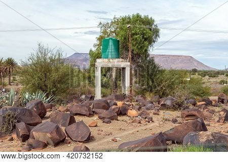 A Water Tank Between Boulders At The Railroad Station At Nelspoort In The Western Cape Karoo. Power