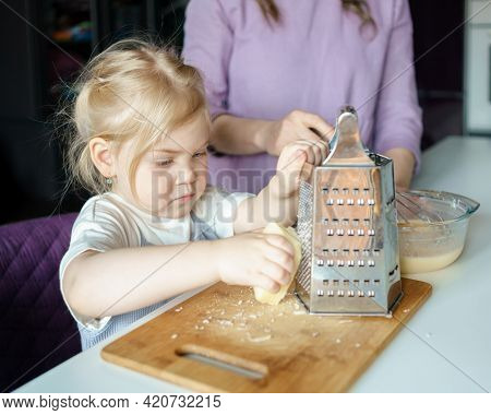 Concentrated Cute Little Girl With Blonde Hair Helping Mom To Cook Omelet In Kitchen, Small Child Da