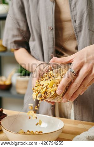 A person in casualwear putting corn flakes into a bowl while preparing breakfast