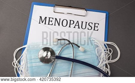Folder With Paper Text Menopause , On A Table With A Stethoscope And Medical Masks, Medical