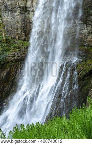 Akarmara, Abkhazia - May 6, 2021: Mountain Cascade Waterfall. Falls Velikan. People Under The Waterf