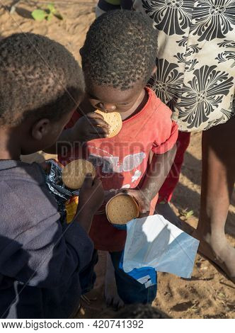 Portrait of hungry African brothers sharing and eating in their yard in a village  in Botswana village