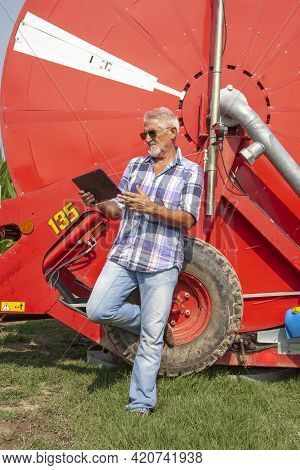 Modern Technological Farmer While Checking The Growth Data Of Corn On The Tablet Of His Cultivated F