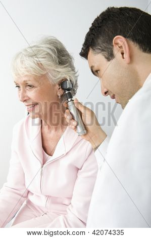 Male doctor checking patient's ear using otoscope poster