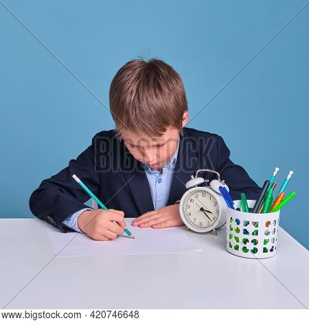 Schoolboy Junior Draws On A Sheet Of Paper At A School Desk, Blue Background