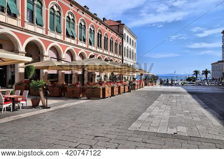 Split, Croatia - July 20, 2019: People Visit Shaded Arcades Of Prokurative Building At Trg Republike