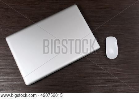 Modern Closed Laptop Computer With Wireless Mouse On Wooden Table