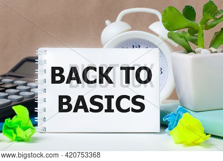 Flower In A Pot, Calculator, White Alarm Clock, Multi-colored Pieces Of Paper And A White Notebook W