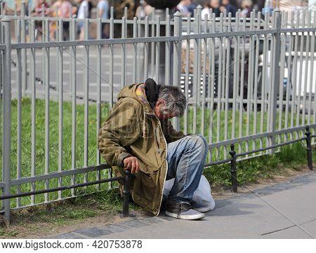 A Homeless Beggar Sits At A Gray Park Fence, Nevsky Prospekt, Saint Petersburg, Russia, May 2021