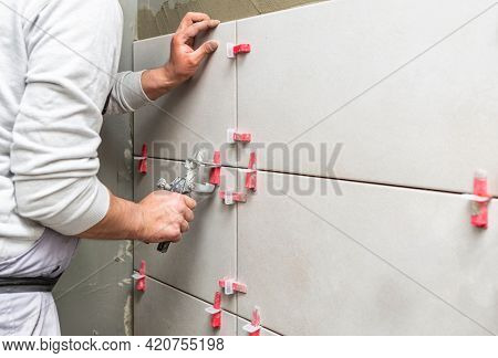 Tiler placing ceramic wall tile in position over adhesive with lash tile leveling system