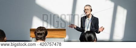 Back View Of Business People Near Discouraged Lecturer Showing Shrug Gesture During Conference, Bann