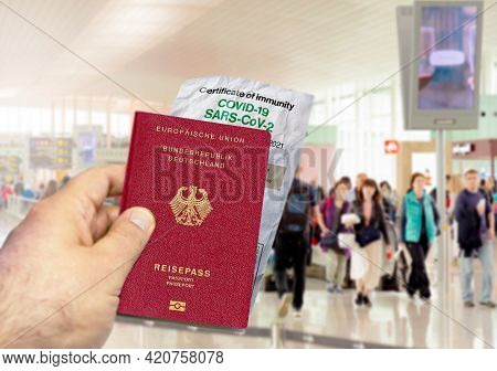 Hand Holding A Germany Passport With A Wrinkled Paper Coronavirus Covid 19 Immunity Certificate. Blu