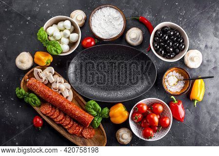 Pizza Ingredients On The Dark Background And Black Plate. Pepperoni Sausage, Mozzarella Cheese, Toma