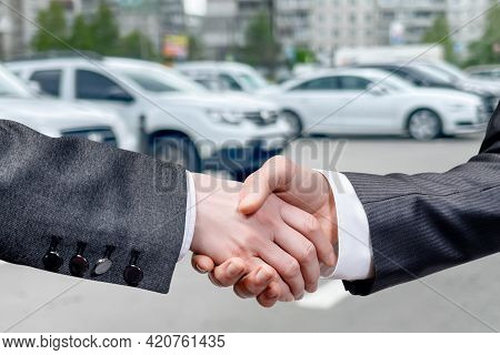 The Concept Of A Successful Car Purchase. Shake Hands On Blurred Background Of Car Parking.