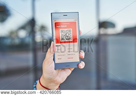 Hand Woman Holds Smartphone Displaying An App Positive Test Result Of Covid-19. Express Pcr Test, Di