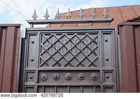 Part Of A Brown Iron Door With A Wrought Pattern And Sharp Bars On The Street