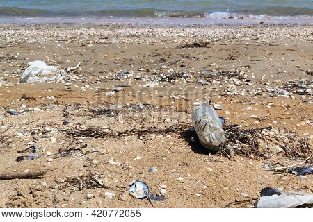 An Old, Semi-decomposed Plastic Bottle Lies On The Seashore Among Shells And Sand.