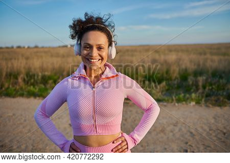 African American Woman With Headphones Putting Her Hands On A Waist, Smiling With Toothy Smile And L