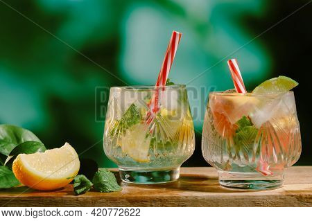 Two Glasses Of Hard Seltzer Alcoholic Cocktail On Natural Summer Background. Refreshing Water With G
