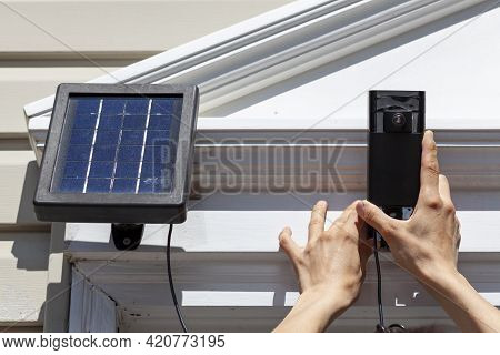 A Caucasian Woman Is Installing A Wireless Security Surveillence Camera With Motion Sensor On Top Of