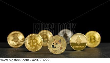 Symbolic Cryptocurrency Types Represented As Shiny Coins Are Lined Up Against Dark Background. Among