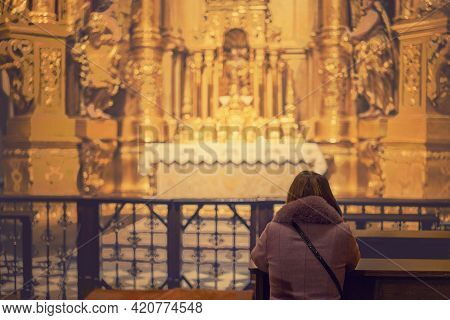 A Woman In A Temple Prays To God. Woman Praying In Front Of Altar. Praying Woman In Front Of Altar.