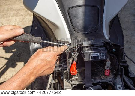 Repair And Dismantling Of A Motorcycle. The Man Unscrews The Fasteners Of The Front Side Trim.