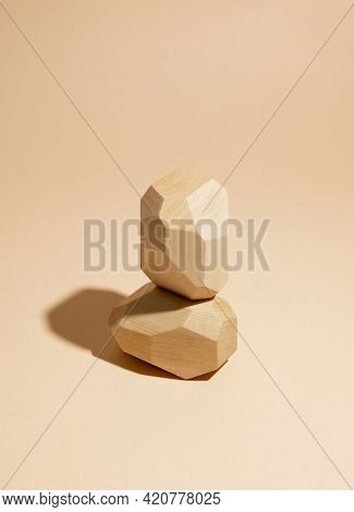 Composition of geometric balancing wooden stones. Concept of balance. Pastel background with copy space.