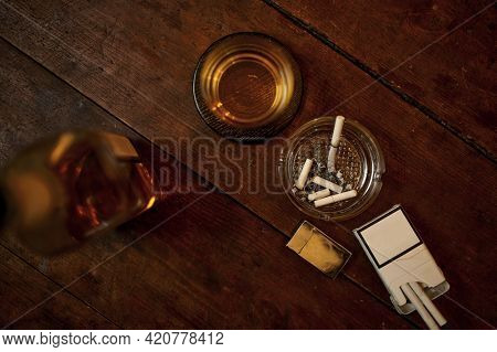 Cigarettes in ashtray, alcohol in bottle, top view