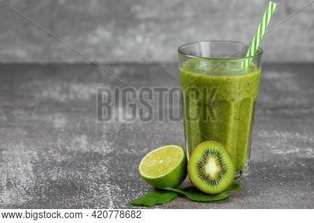 Fresh Healthy Smoothie Drink In A Tall Glass Glass With A Straw Surrounded By Fruits On A Gray Concr