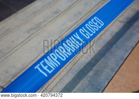 Temporarily closed caution tape. Closed due to Covid-19. Information notice sign about quarantine measures. Close up on a closed caution tape. Blue and White Caution Tape.