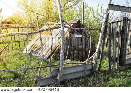 Old Hut. A Collapsed House With An Old Fence. Abandoned House.