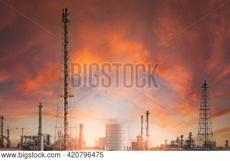 Oil Refinery Or Petroleum Refinery Plant With Red Sunset Sky Background. Power And Energy Industry.