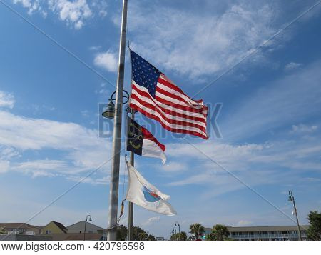The Us, North Carolina State, And The Sunset Beach, Nc Flags On A Pole Flapping In The Wind. This Is
