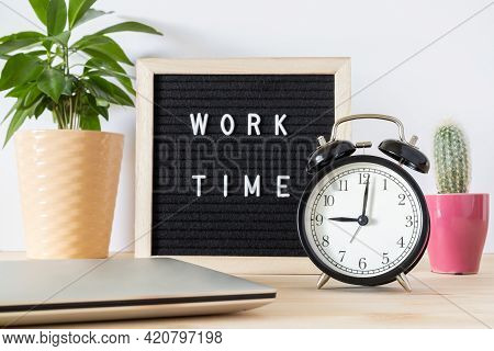 Classic Black Alarm Clock, Laptop And Black Board With Words 'work Time' On Wooden Table Against Whi