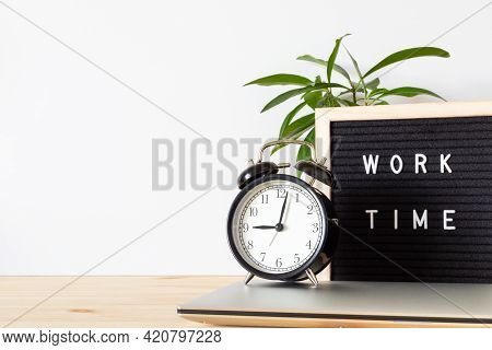 Classic Black Alarm Clock, Laptop And Black Board With Words 'work Time' On Wooden Table With White