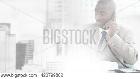 Composition of cityscape over african american businessman using phone. global business, finance and networking concept digitally generated image.