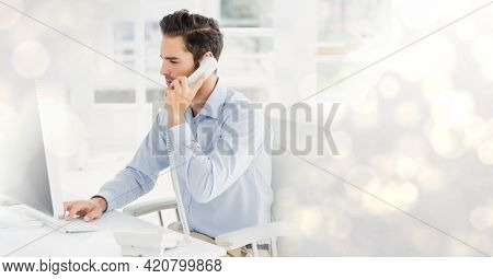Composition of light circles over businessman using computer and phone. global business, finance and networking concept digitally generated image.