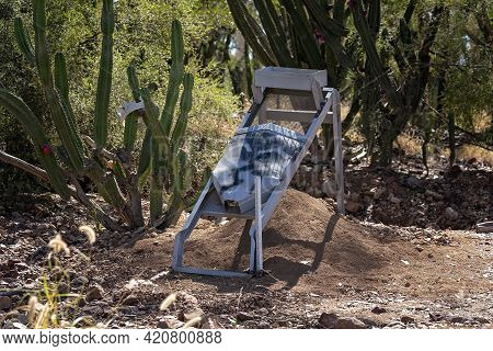 Abandoned Sapphire Mining Sieve Amongst Rocks And Cacti On Fossicking Field