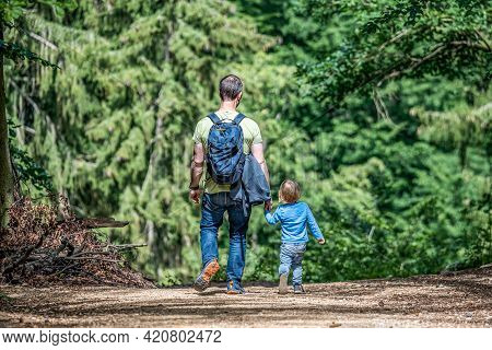 Father Holding Hand Of Little Son With Backpack Hiking In Forest