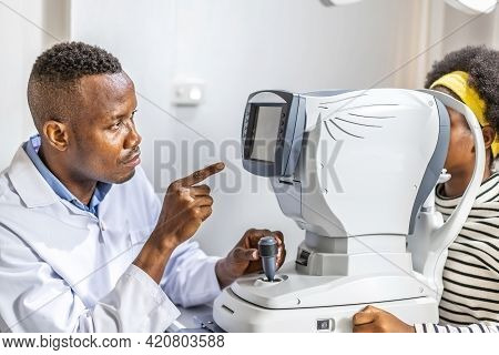 Male Doctor Ophthalmologist Is Checking The Eye Vision Of Black African American Teen Girl In Modern