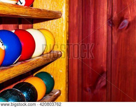 Colored Billiard Balls On A Wooden Shelf. Billiard Ball. Wooden Shelf. Numbered Balls. Gambling. Spo
