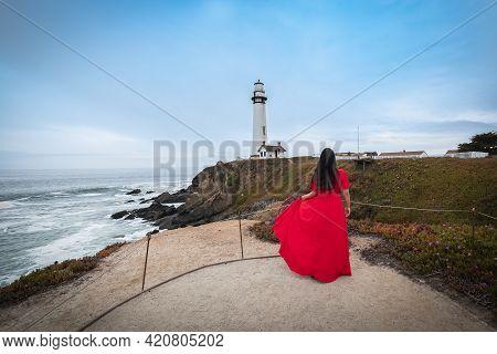Yong Beautiful Brunette Woman In A Long Elegant Red Dress Posing Near The Pacific Ocean On Californi