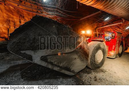 An Underground Loading Machine Carries A Full Bucket Of Ore. Special Low-profile Equipment For Under