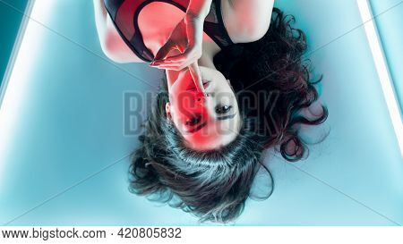 Beauty Secret. Aesthetic Cosmetology. Plastic Surgery. Red Neon Light Brunette Woman With Perfect Fa