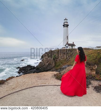 Yong Beautiful Brunette In A Long Red Dress Posing On California Coast With A Lighthouse In The Back