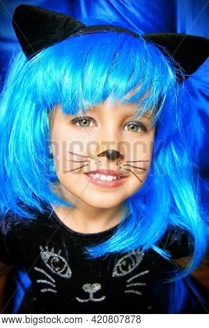Close-up portrait of a cute little girl child in cat costume and bright blue wig smiling at camera. Halloween party. Carnival costume.